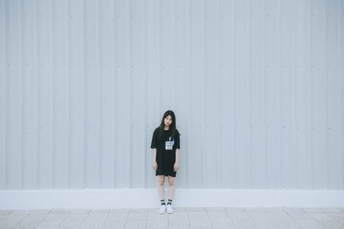 Woman in Black Elbow Sleeve Shirt and Black Shorts Standing Behind White Wall