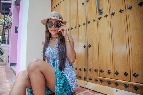 Woman in Blue and White Sleeveless Dress Wearing Brown Sun Hat Sitting on Brown Wooden Cabinet