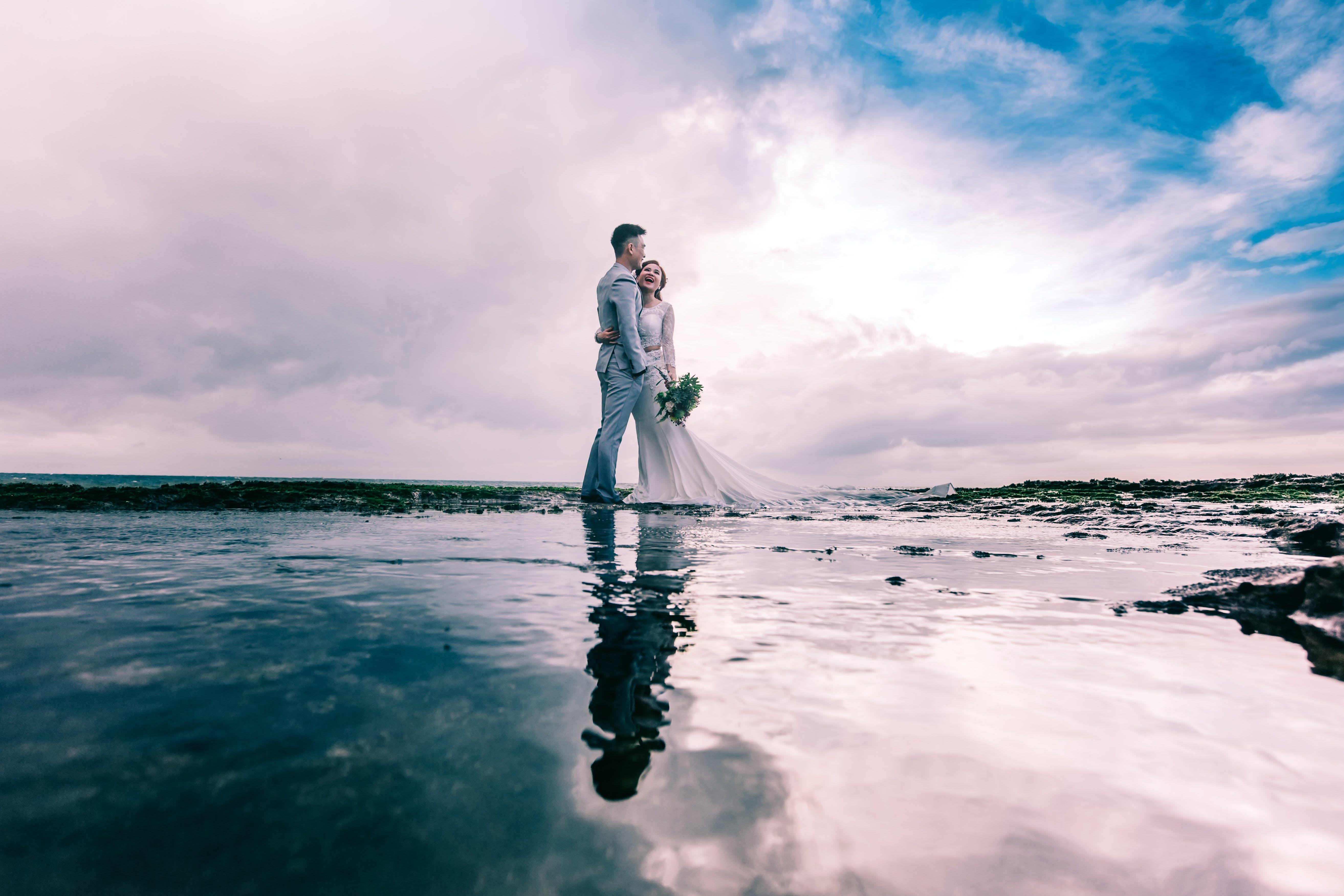 Man in Gray Dress Suit Jacket Embraces Woman Wearing Wedding Gown