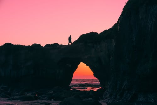 Silhouette of Man on Rock Walking during Nightime