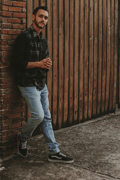 Man in Black Dress Shirt and Blue Denim Jeans Standing Beside Brown Wooden Wall