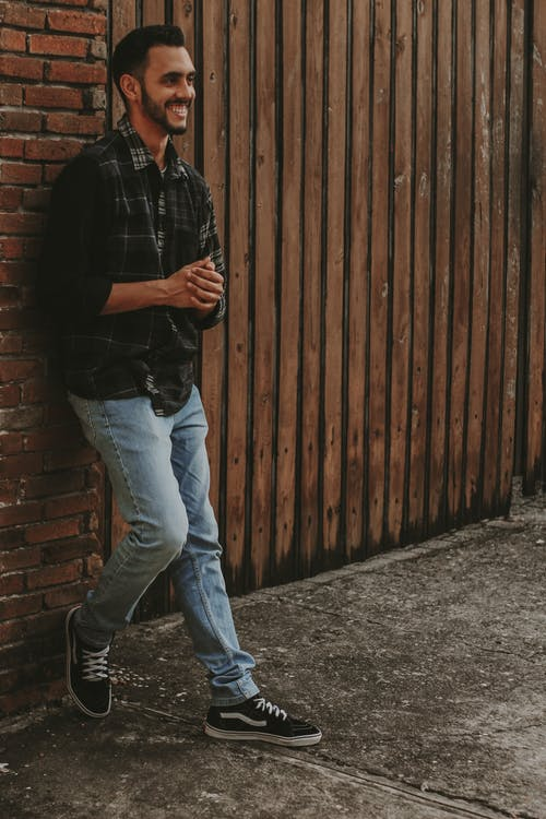 Man in Black Polo Shirt and Blue Denim Jeans Standing Beside Brown Wooden Wall