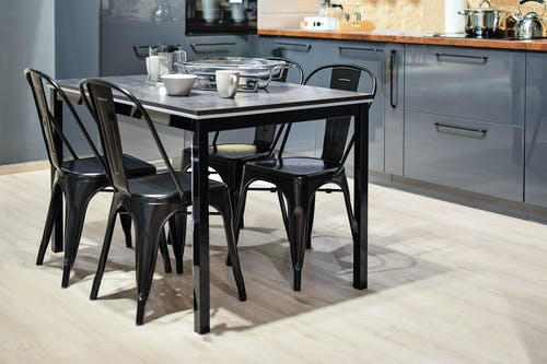 White Ceramic Mug on Black Dining Table With Four Chair Set