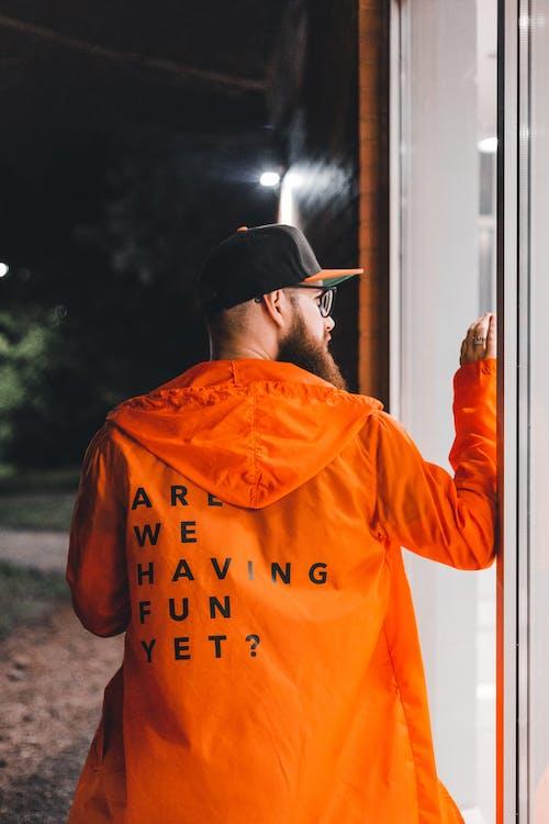 Man in Orange and Black T-shirt Wearing Black Cap