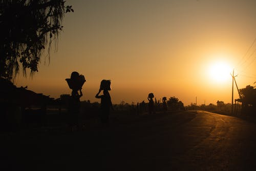 Silhouette of People Walking on Road during Sunset