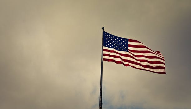 selective focus photography of u s a flag on poles free stock photo