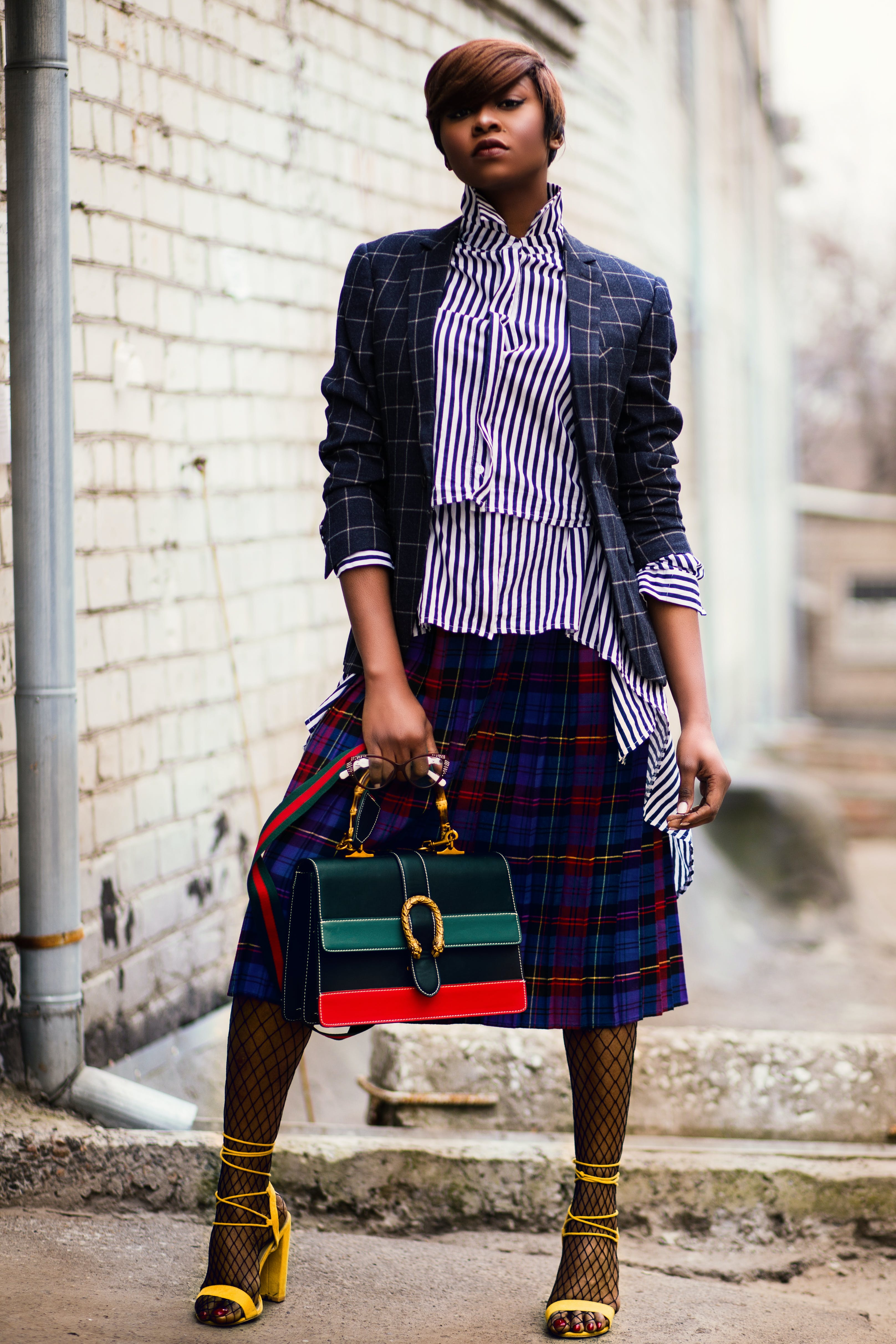 Woman in Blue and White Plaid Cardigan Holding Green and Red Handbag