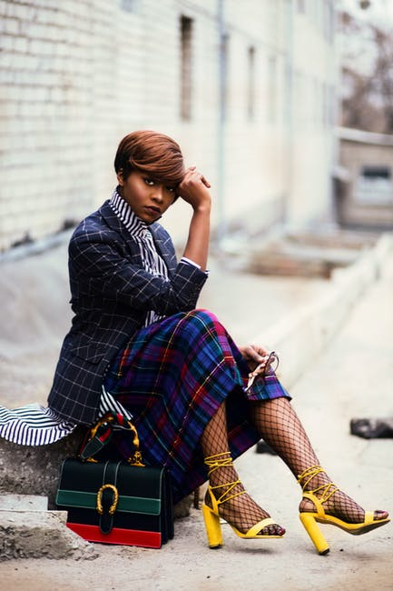 Woman Wearing Black and Grey Tattersall Blazer and Multicolored Plaid Skirt With Black Mesh Stocking and Yellow Chunky Heeled Sandals Sitting on Grey Concrete Pathway