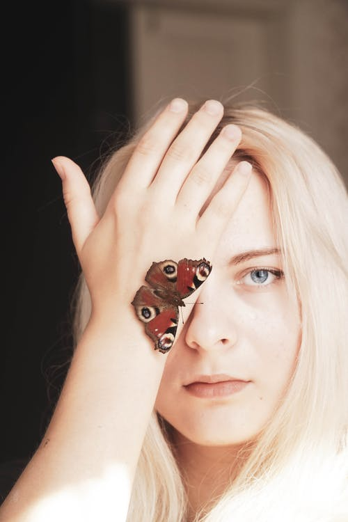 Woman With Brown and Black Butterfly on Her Hand