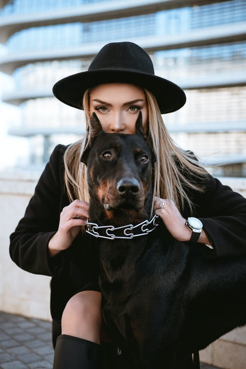 Woman in Black Jacket Holding Black and Brown Short Coated Dog