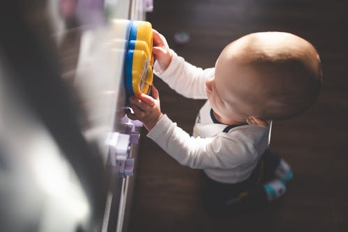 High-Angle Shot of a Kid Playing with a Blue and Yellow Toy