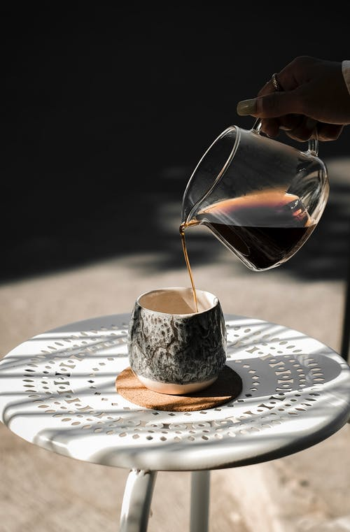 Person Pouring Water on White Ceramic Teacup