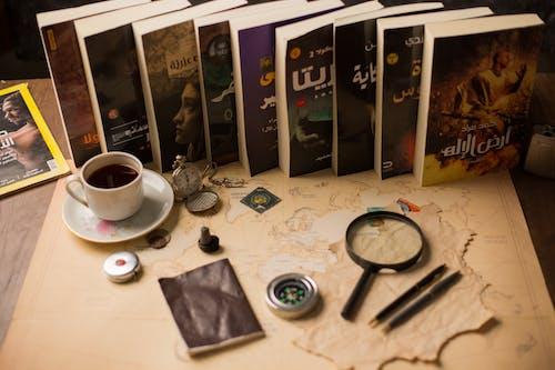 White Ceramic Mug Beside Black Magnifying Glass on White Table