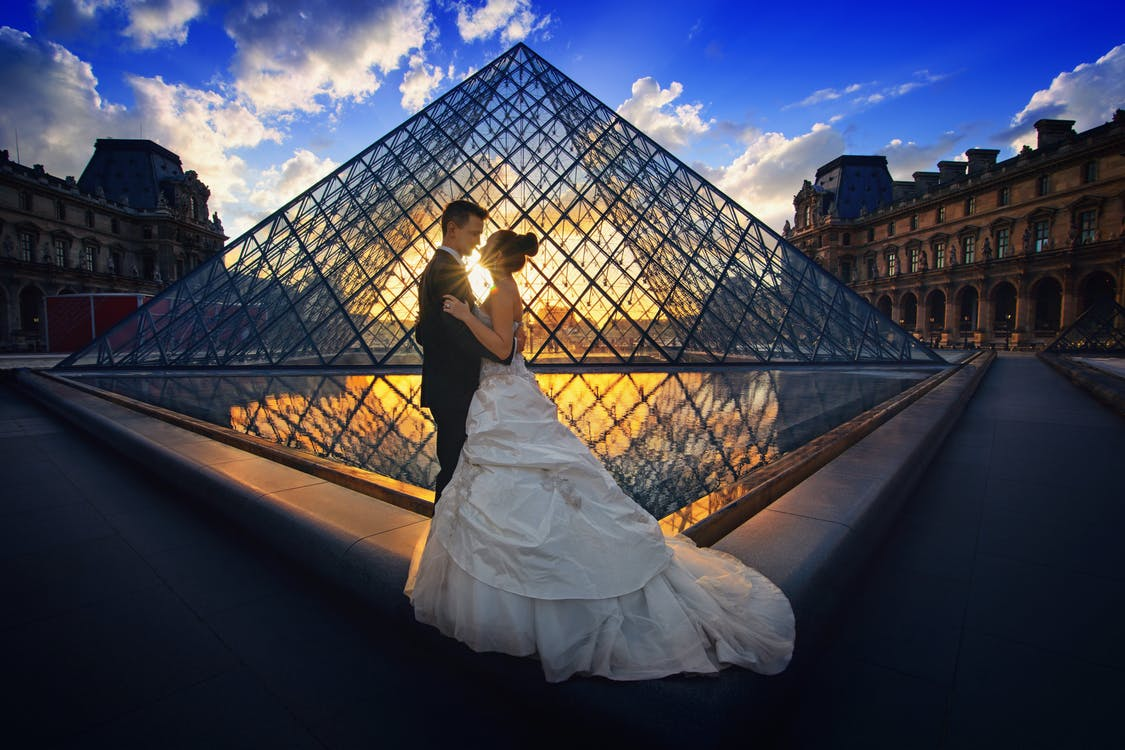 Photography of Man and Woman at the Lourve Museum during Sunset