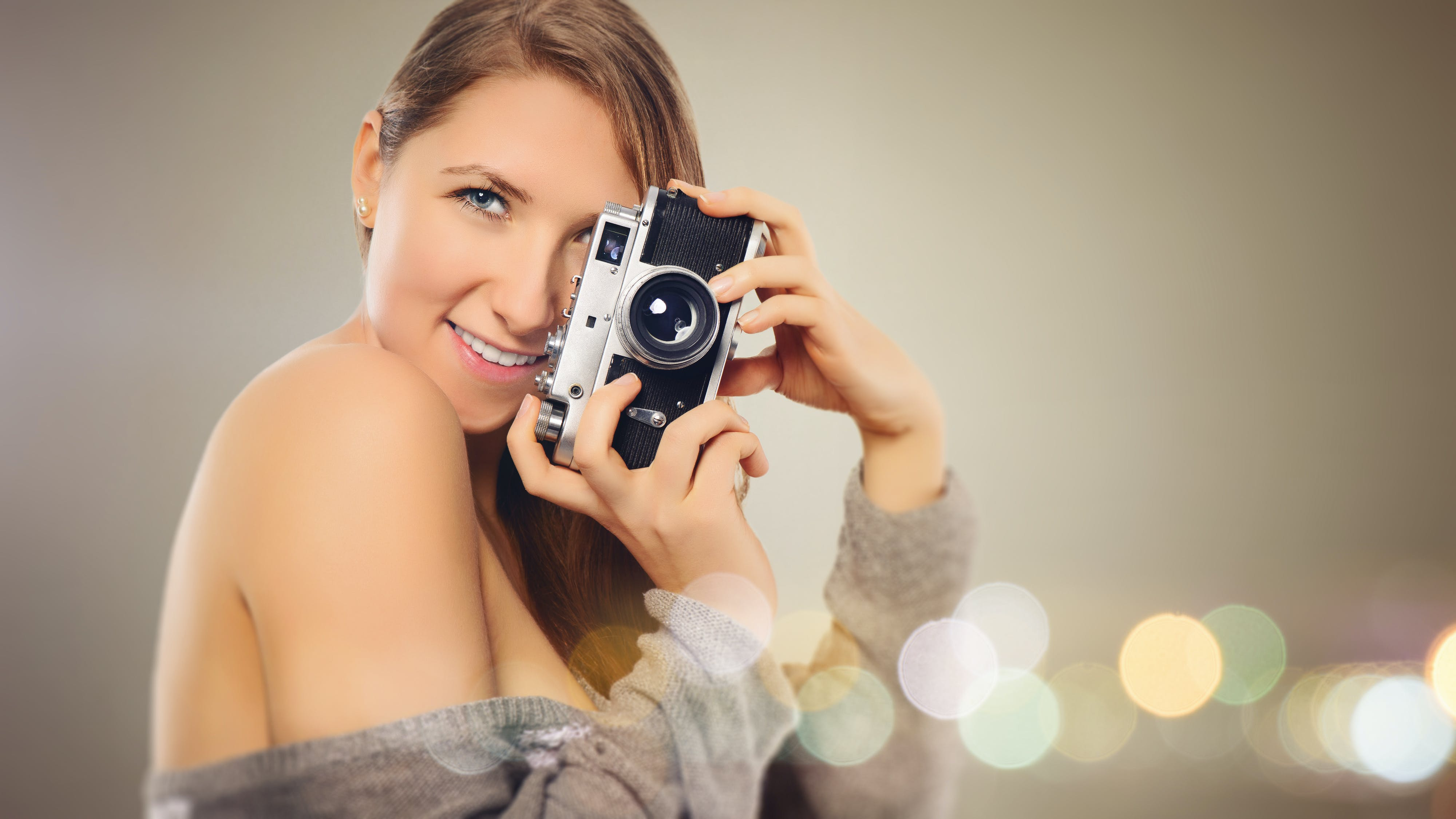 Woman With Gray Dress Holding Camera