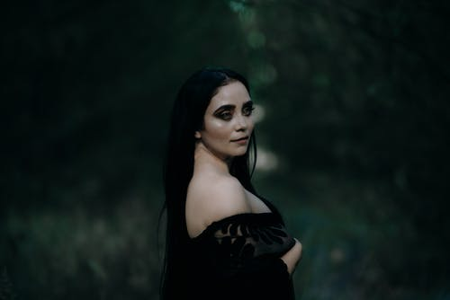 Woman in a Black Off Shoulder Dress Looking at the Camera