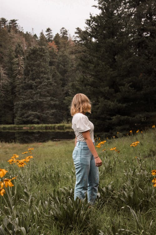 Woman in a White Top and Denim Jeans Standing in a Meadow