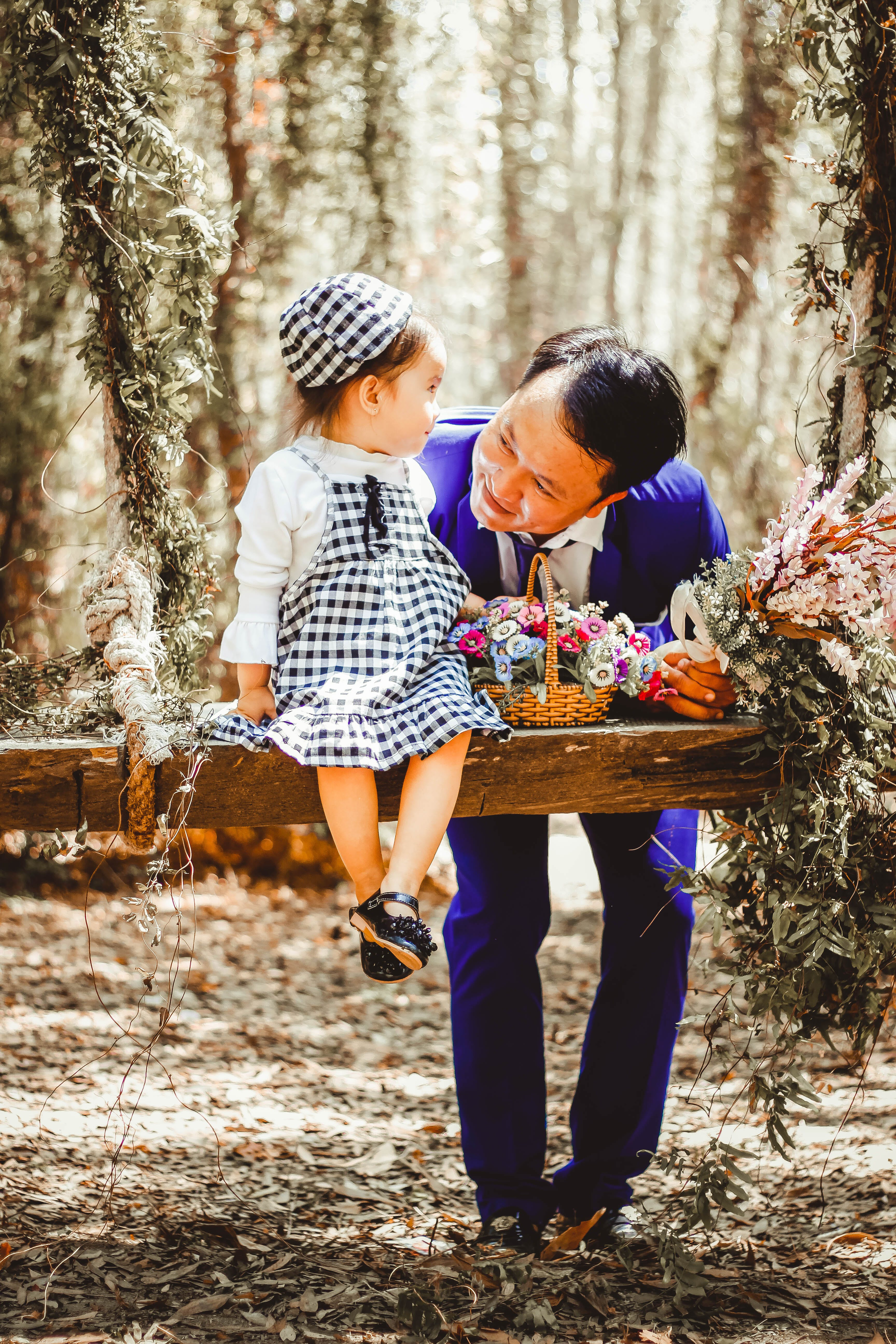 Selective Focus and Color Photography of a Dad Looking at Her daughter Sitting on Garden Swing White Holding Bouquet of Flower in Brown Wicker Basket