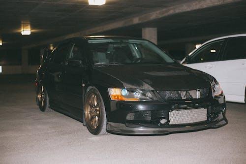 A Black Mitsubishi Lancer Evolution in a Parking Lot