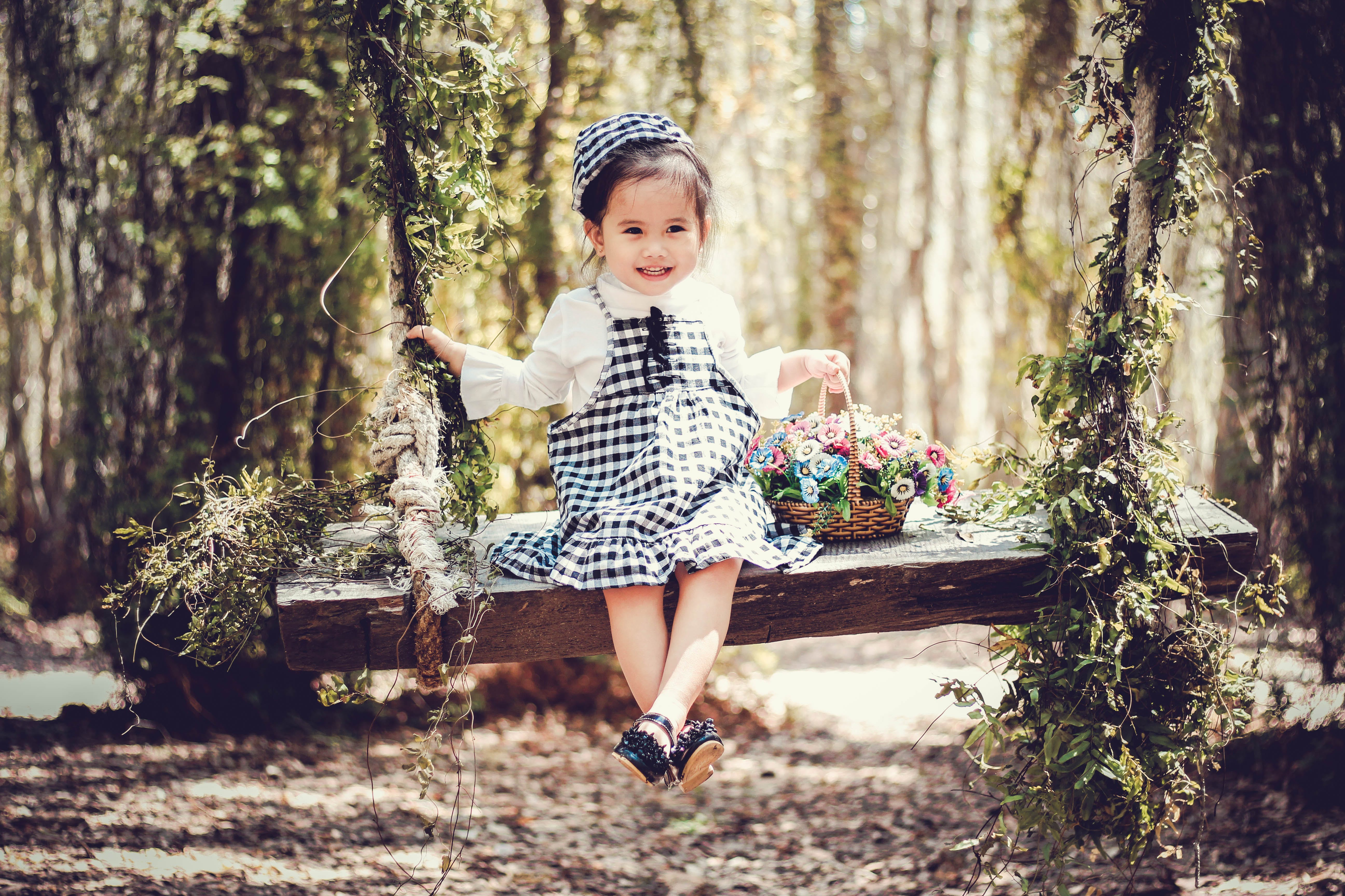 Girl in Black and White Overall Skirt Holding Basket With Petaled Flowers