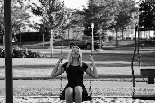 Woman in Black Tank Top Sitting on Swing Chair