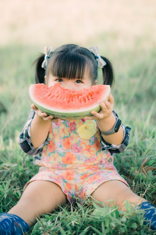 Girl in Yellow and White Floral Dress Eating Watermelon