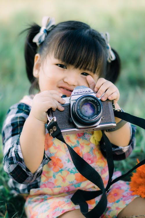 Girl in Blue and White Plaid Shirt Holding Black and Silver Dslr Camera