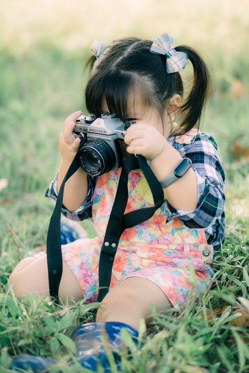 Girl in Blue and White Plaid Shirt Lying on Green Grass Field Using Black Dslr Camera