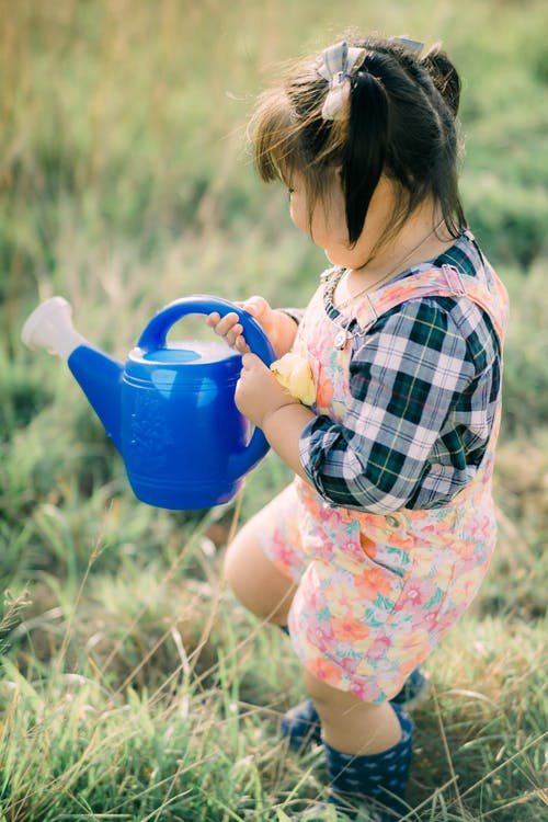 Cute Kid Holding a Blue Watering Can