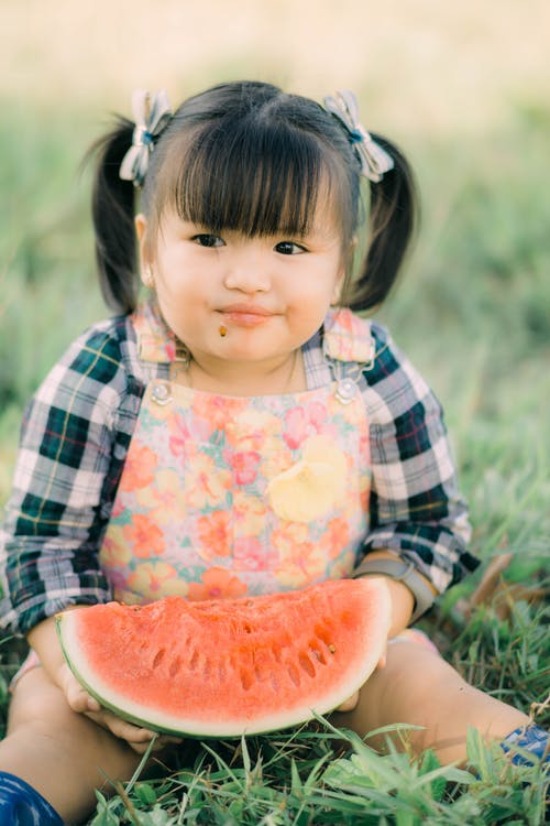 Adorable Kid Sitting on the Grass while Eating a Watermelon