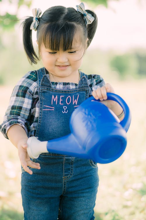 Boy in Red and Black Plaid Shirt Holding Blue Plastic Pitcher