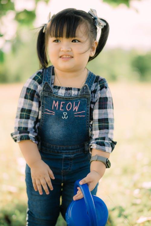 Selective Focus Photo of a Cute Kid in a Blue Denim Jumper