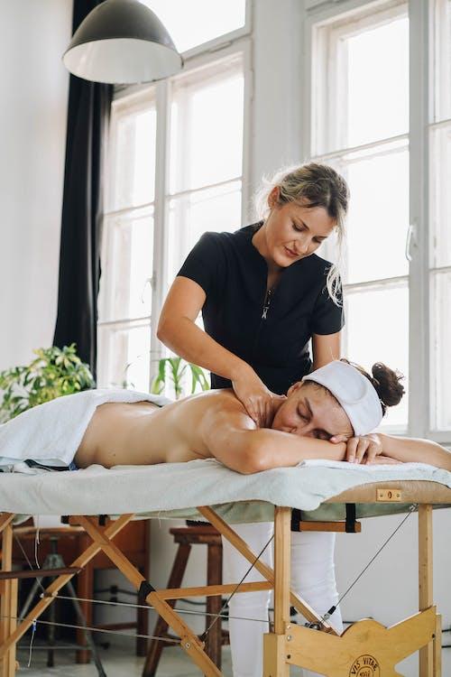 Woman in Black Shirt Massaging Womans Foot