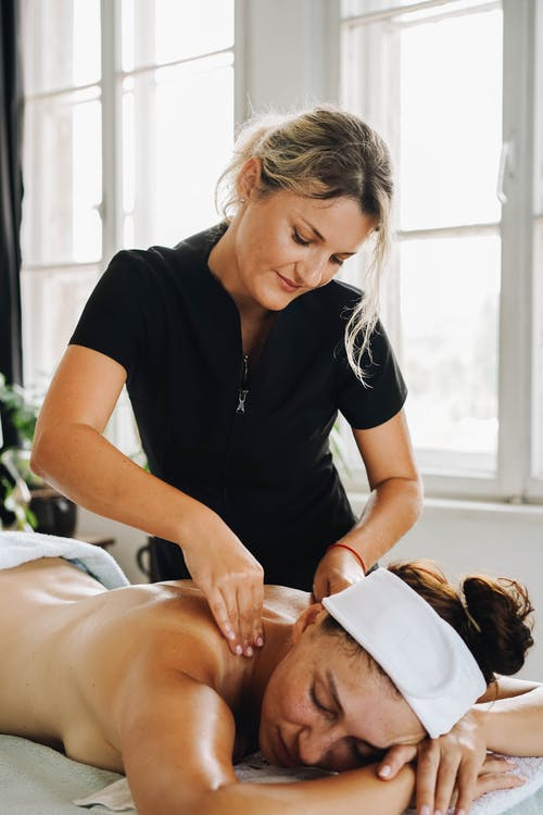 Masseuse in a Black Polo Shirt Massaging a Woman's Back