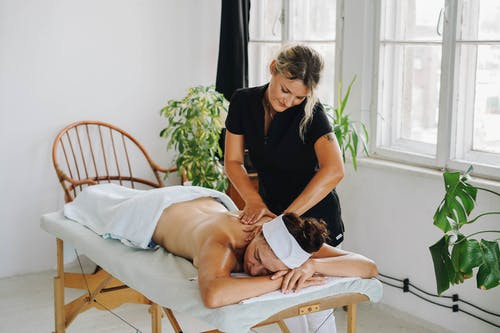 Topless Woman Getting a Back Massage
