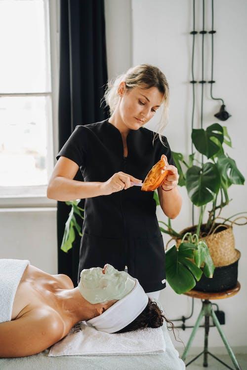 Woman in Black T-shirt Holding Orange Fruit