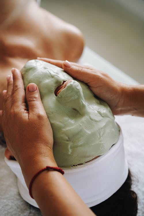Person Holding White and Green Cream