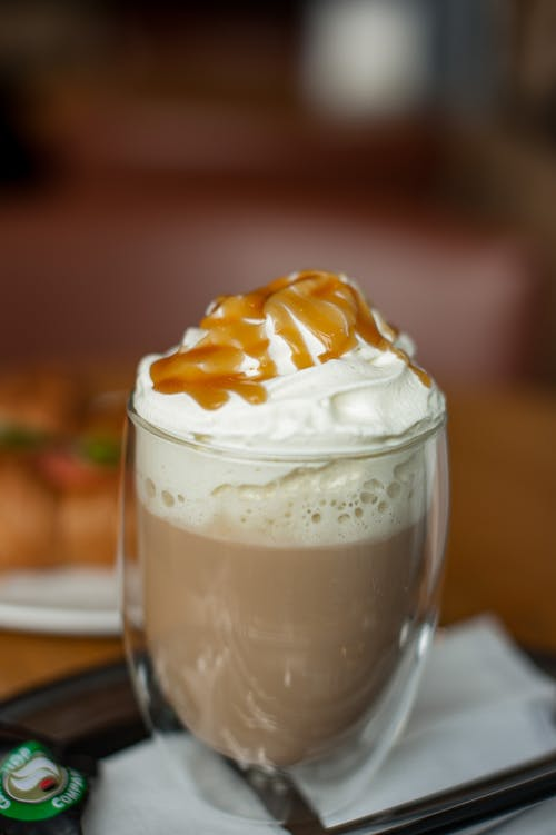 Close-Up Photo of a Mocha Drink with Whipped Cream and Caramel on Top
