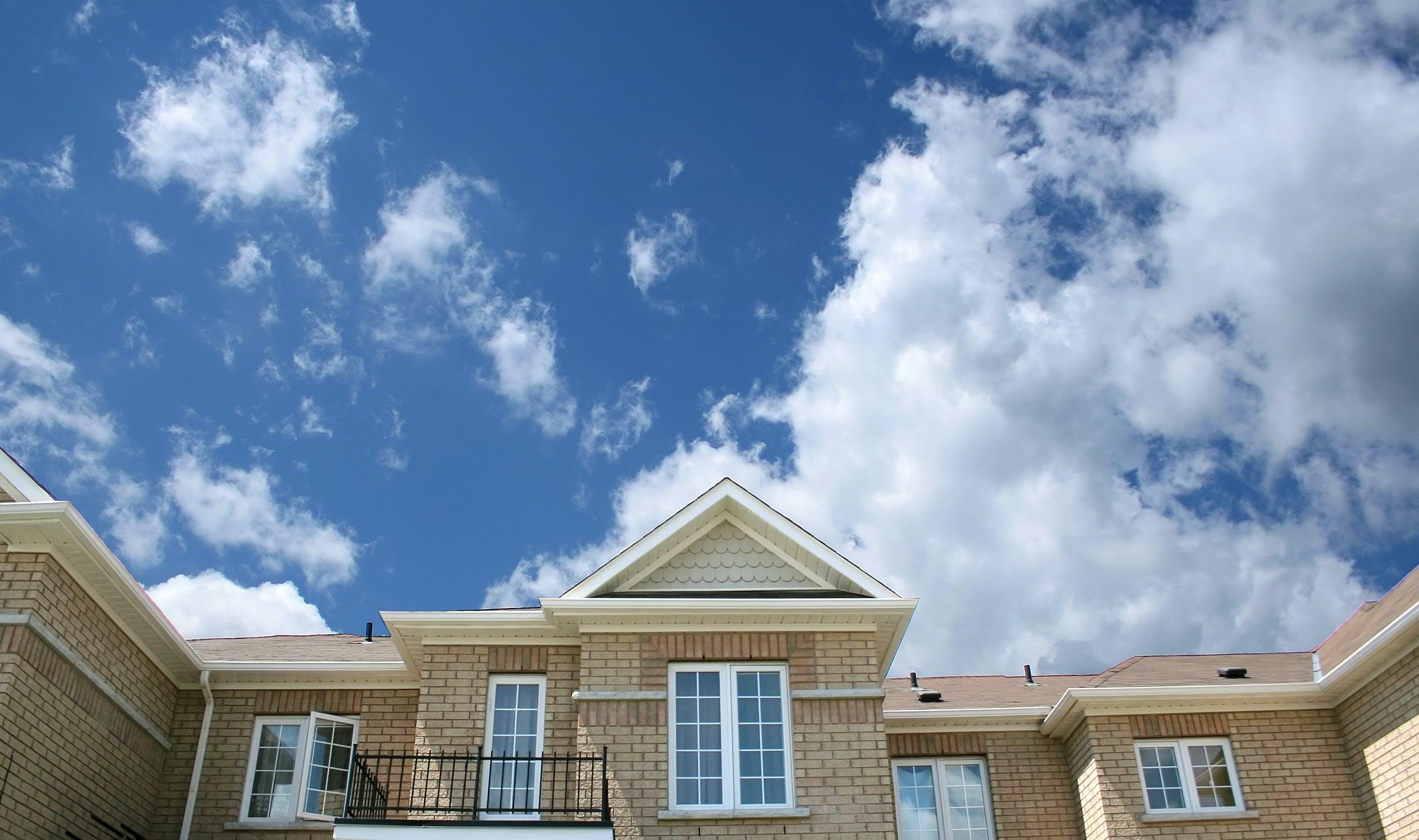 Brown Bricked House Under Cloudy Skies