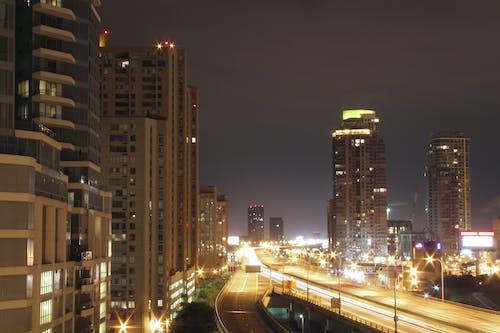 Foto profissional grátis de arranha-céus, edifícios, estrada, fachos de luz