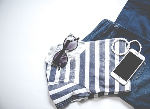 Photo of Iphone on Shirt Near Sunglasses