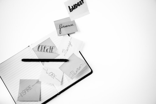 Grayscale Photo of Lined Paper Notebooks and Pen
