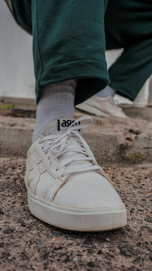 Close-Up Photo of White Sneakers on a Concrete Pavement