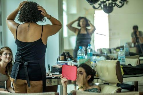 Женщина в черном топе с бретельками рядом с женщиной, держащей розовое зеркало