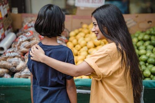 Woman in Yellow T-shirt Holding Yellow Fruit