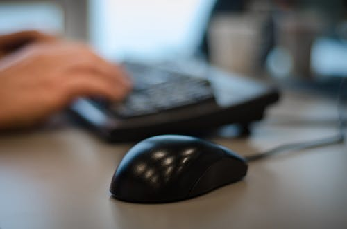 Selective Focus Photography of Black Mouse on Desk