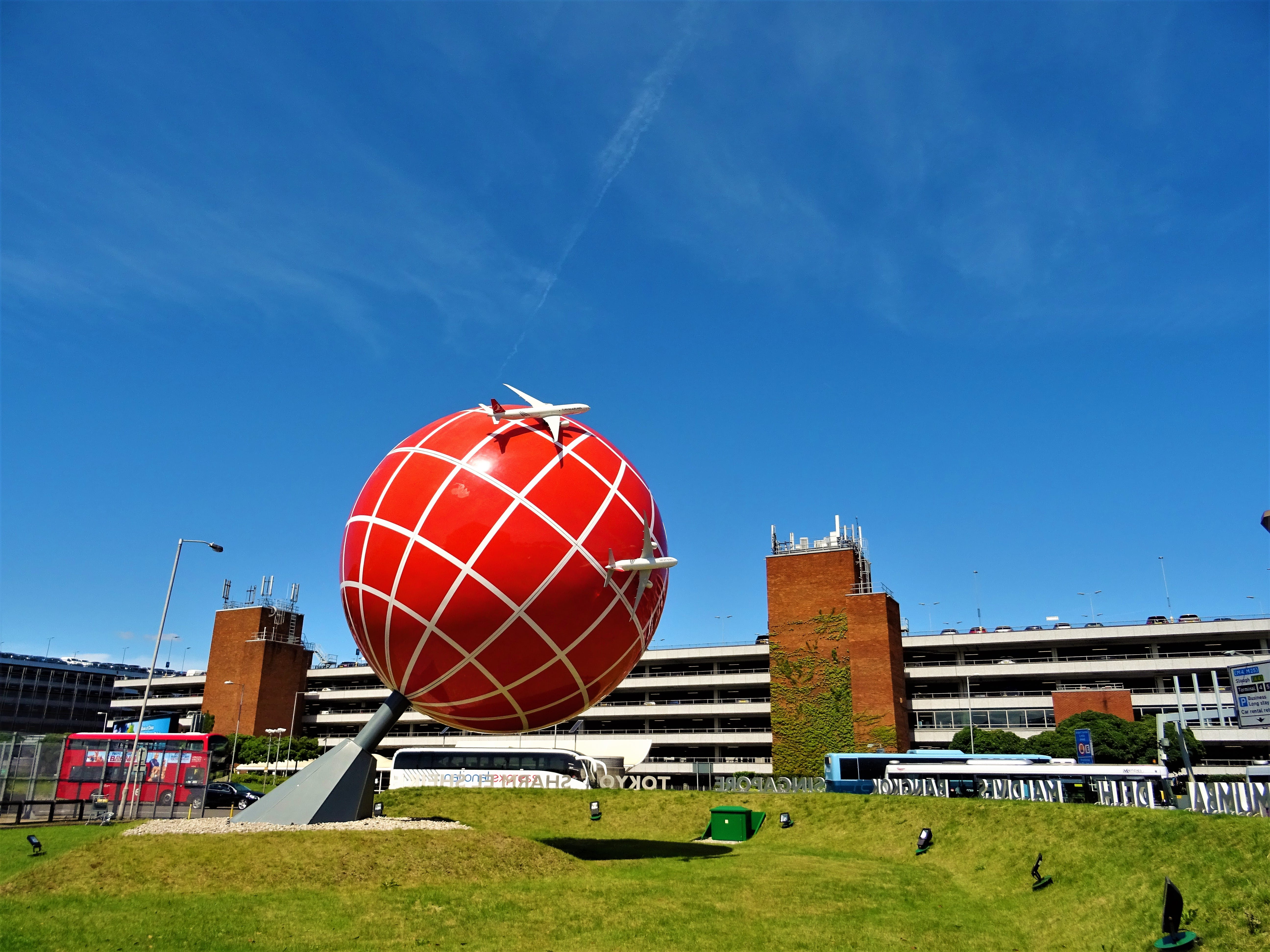 Red and White Globe Statue Near Brown and White Concrete Building