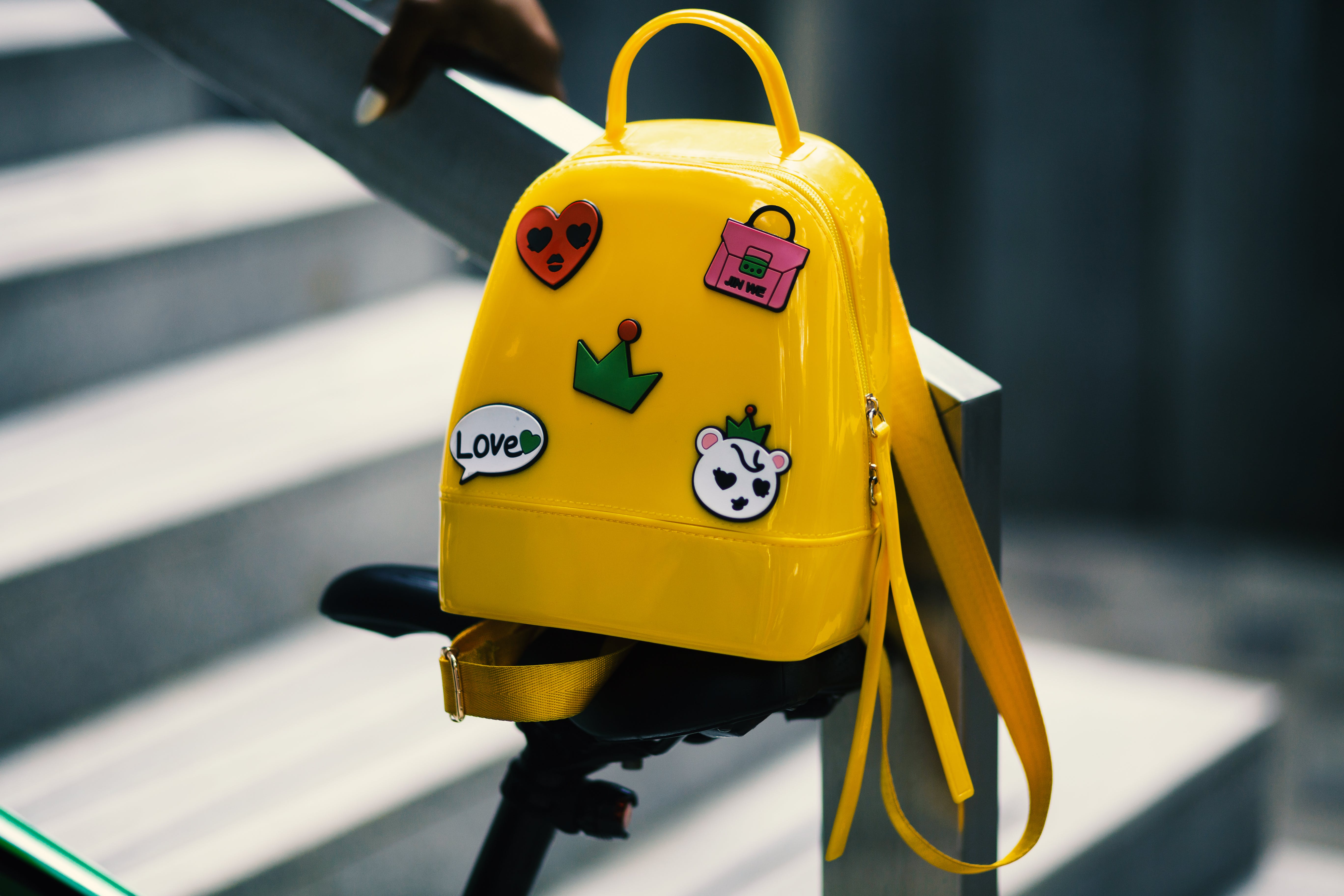 Yellow Backpack With Five Assorted Stickers on Grey Metal Stairway Rail