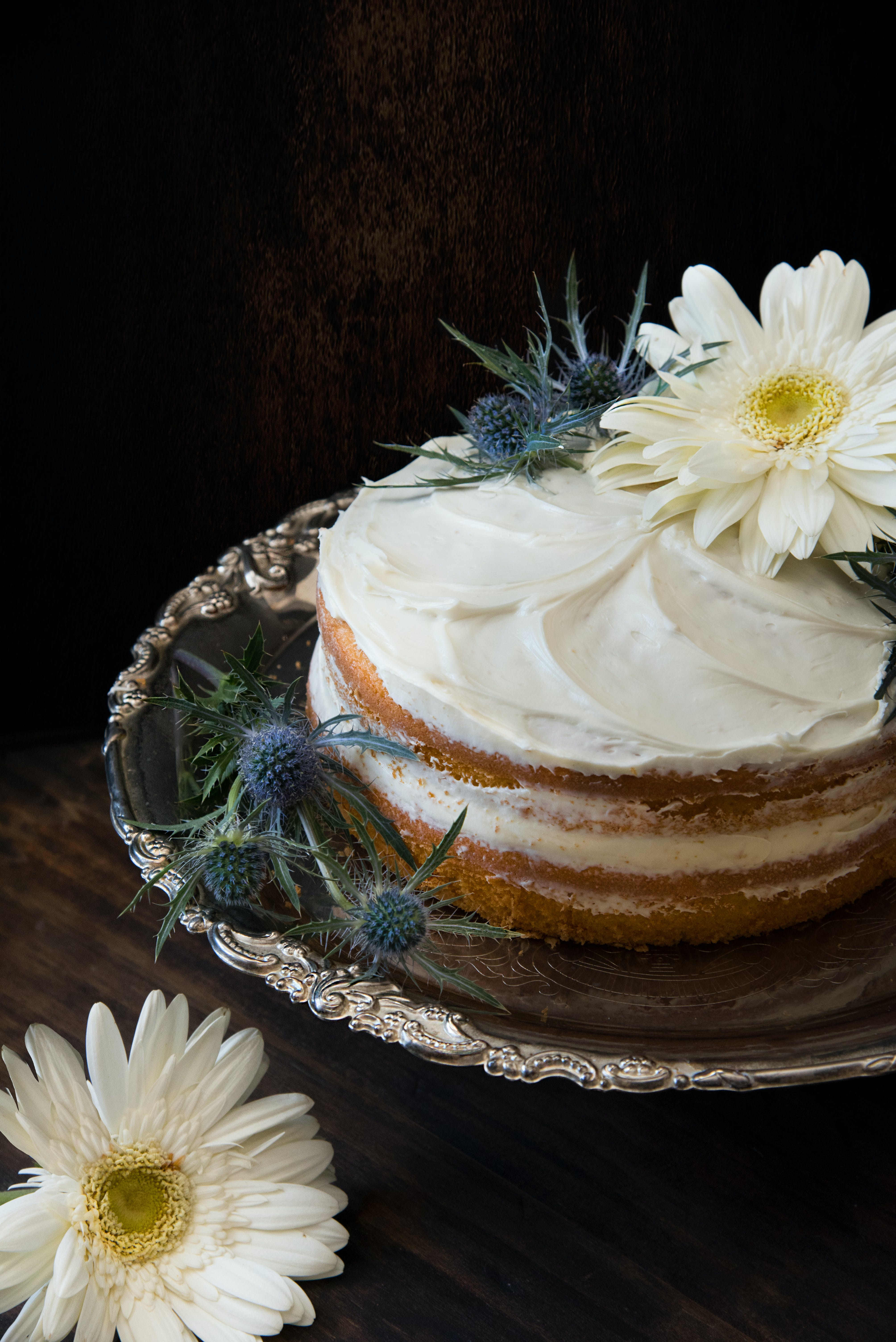 Fondant Cake Whipped With White Icing and Topped With White Petaled Flower on Grey Stainless Steel Plate