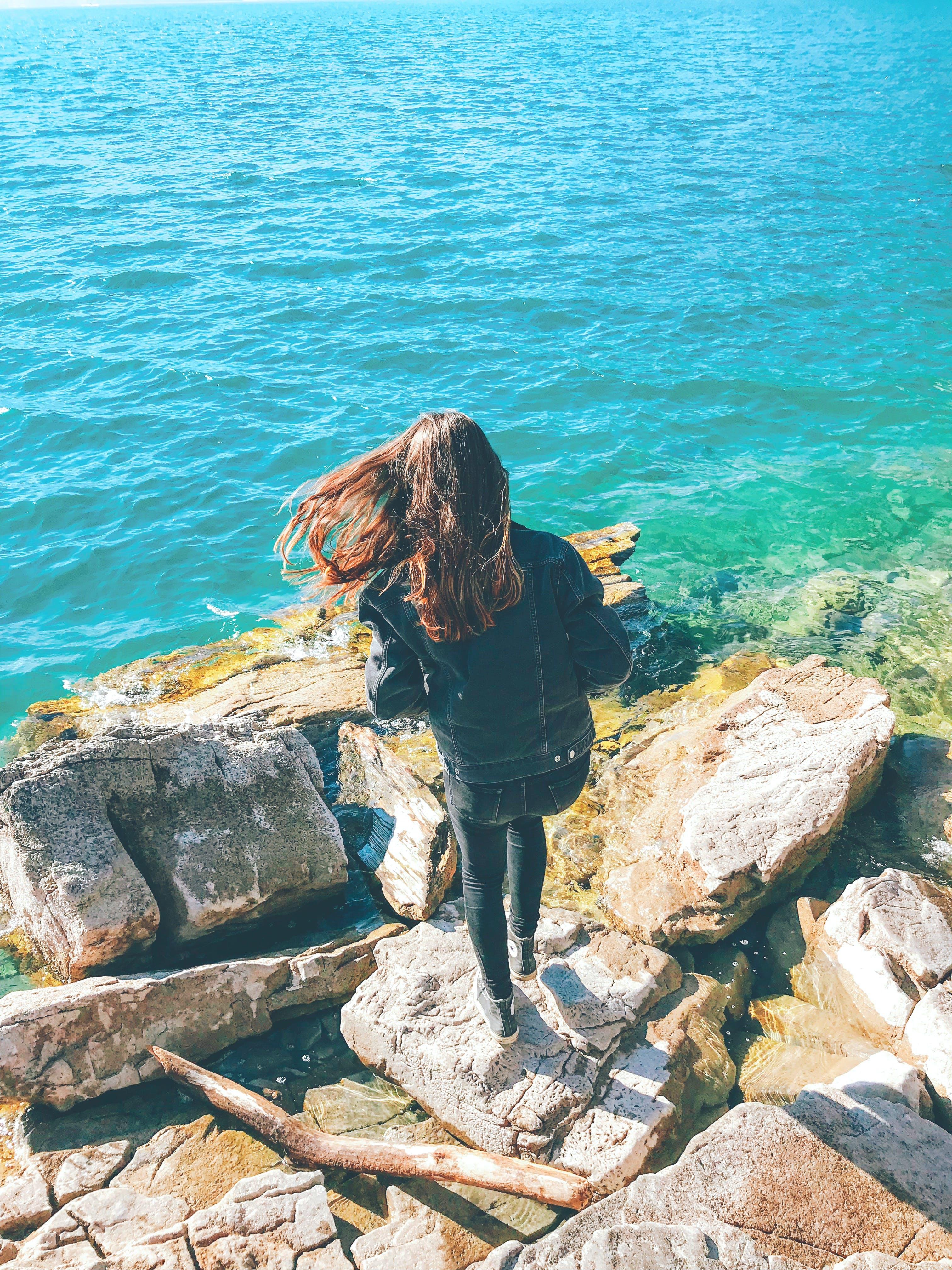 Woman Wearing Denim Jacket Standing on Rock Near Body of Water